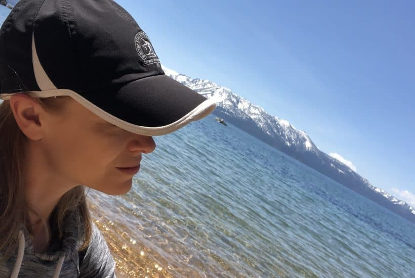 Woman sitting on the shoreline of Lake Tahoe staring out into the blue waters with snow-capped mountains in the background. She is wearing a black hat with a white rim, and you can't see her face directly.