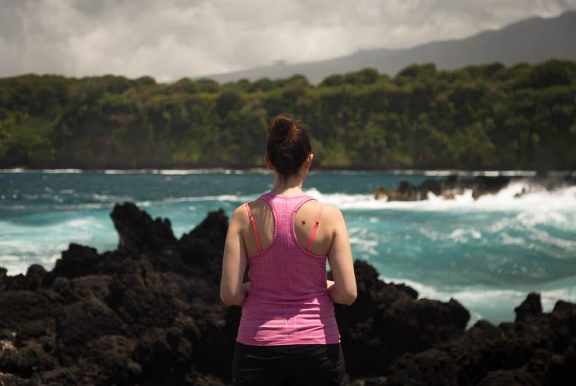 woman in pink tank looking off into the distance with a lake and mountains landscape