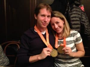 Man with short brown hair with a close-mouth smile wearing a black long-sleeve with a medal around his neck holding it in his hand, next to a woman with medium brown hair and a smile wearing a white and gray short-sleeved shirt wearing a medal around her neck and holding it in her hand.