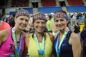 Three women standing and smiling after running the Fargo Marathon with medals around their necks and each wearing the same colorfully designed headbands. One woman is in a pink tank, another in yellow, and the third in blue.