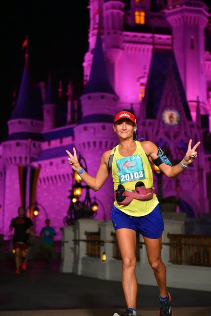 woman giving peace signs with both of her hands in front of the Disney world castle, wearing a yellow tank and blue shorts and a red hat after running the Disney race