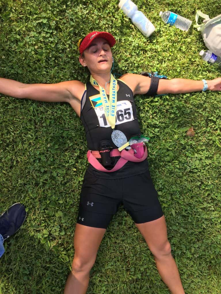 woman laying sprawled out on the grass after finishing a running race, wearing a black tank, black shorts, a red hat, and a medal around her neck
