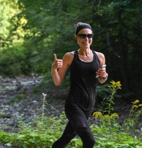 woman smiling and running in nature giving a thumbs up, wearing a black headband, black tank, and black capris holding her phone in her other hand.