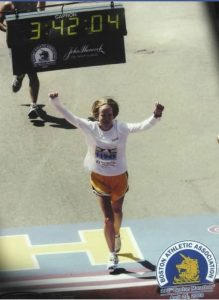 Woman in a white long-sleeve shirt and orange shorts with her arms raised above her head running across the Boston Marathon finish line