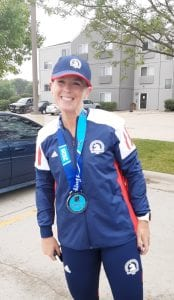 Woman smiling in a parking lot with a blue Boston Marathon hat, red, white, and blue Boston Marathon jacket, and a medal hanging from her neck.
