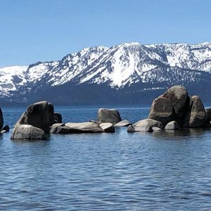 Lake Tahoe picture of blue waters with large rocks jetting out in the middle and snow-capped mountains in the background.