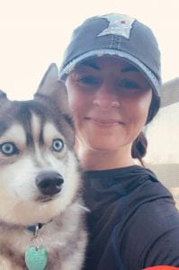 Woman holding a gray and white husky puppy, woman wearing a Minnesota jean hat and wearing black. Hair pulled back.