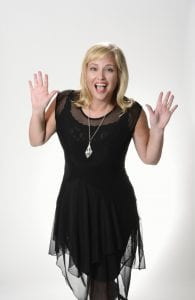 woman smiling with medium blonde hair wearing a black dress and black lace flowing with a silver necklace. Her arms are bent up with her palms out and a smiling surprise face