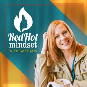 Yellow and Teal background with the Red Hot Mindset logo a white flame with a face in it and a woman with medium length red hair smiling touching her hair with one hand and a khaki jacket