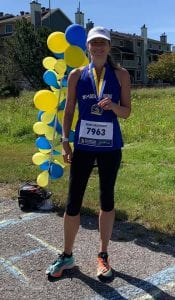 Woman smiling holding the blue and yellow medal around her neck, wearing a blue tank and black capri workout pants. Blue and yellow balloons are in the background as she finished the virtual Boston Marathon.