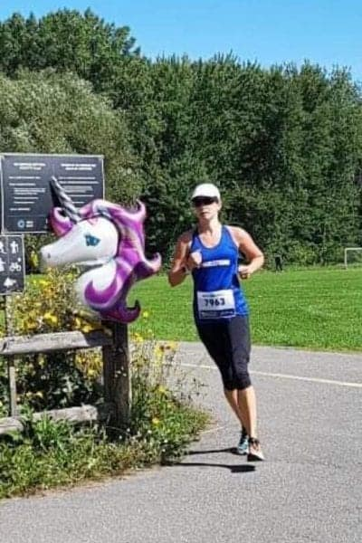 woman in a blue tank and black capri workout pants running around a corner with a fence that has a white and purple unicorn head resting on it