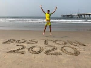 "woman in a yellow tank and yellow shorts jumping in the air at the beach with her arms raised above her head and the words ""Boston 2020"" etched into the sand below"