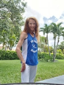 woman with long red hair standing sideways outside in nature with green trees and grass in the background, wearing her running clothes, a blue and white tank top and gray shorts.