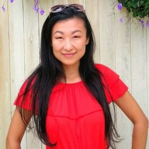 asian woman with long black hair smiling with her mouth closed in front of a light wood paneling, wearing a bright red short-sleeved shirt and sunglasses on her head.
