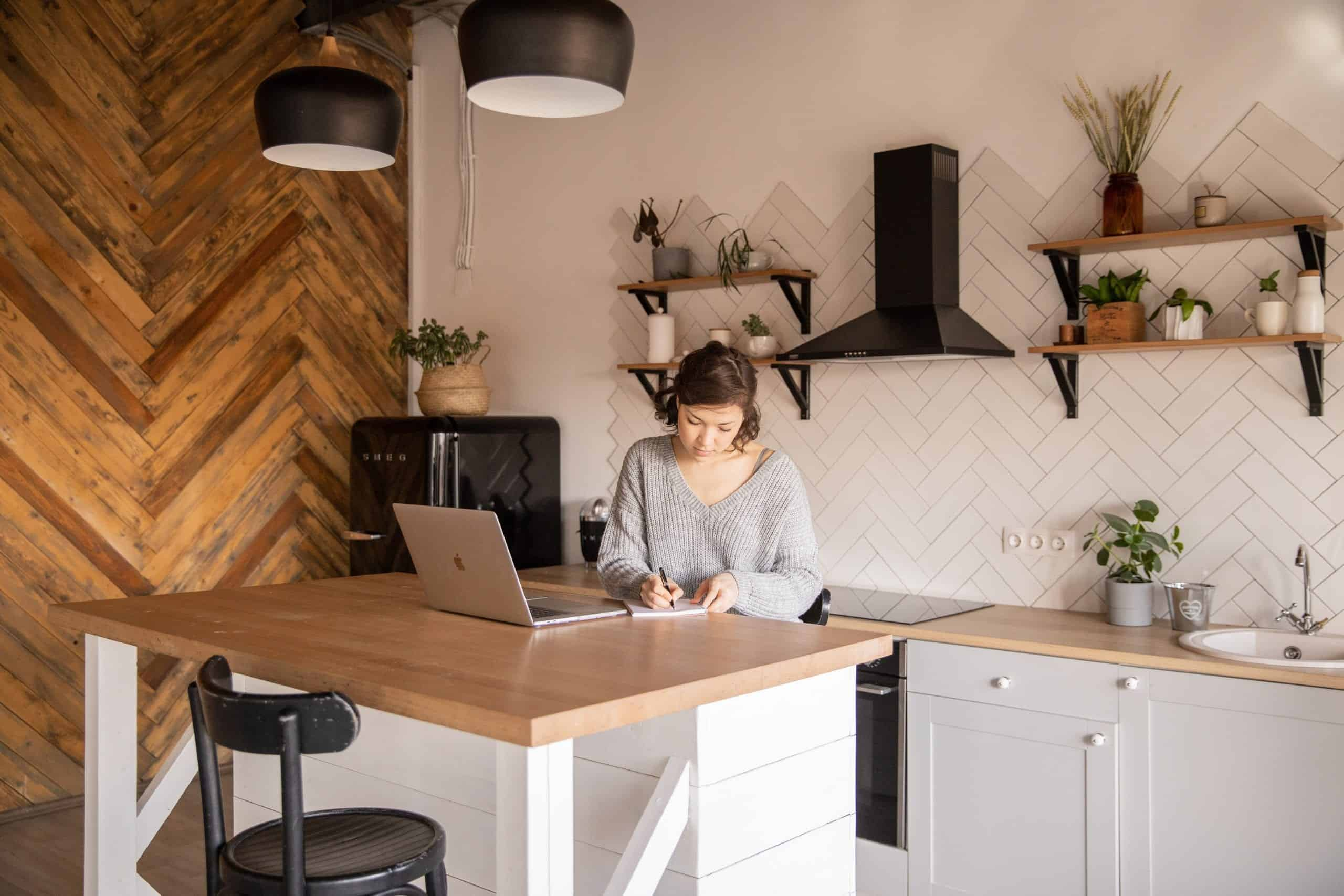picture of woman sitting in her kitchen working with her computer open and open shelving with plants and jars behind her.