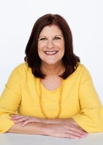 woman with medium brown hair smiling, wearing a bright yellow blouse and a long yellow beaded necklace