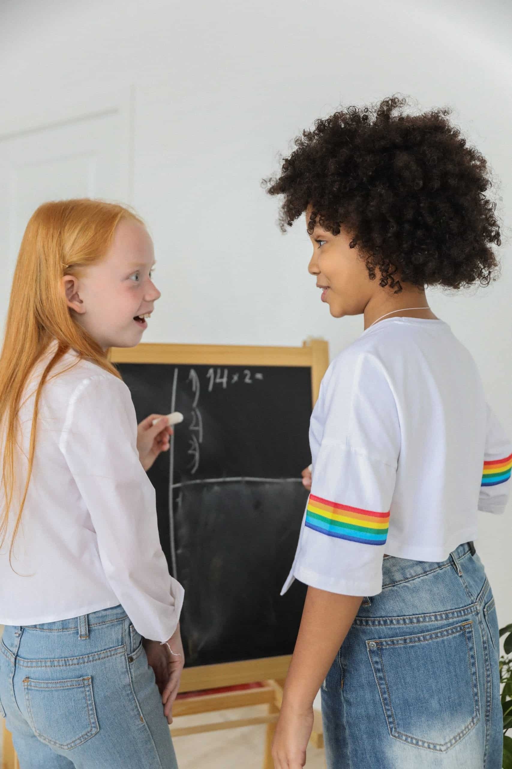 Two girls looking at each other and smiling while doing math problems on a chalkboard. The girl on the left has long red hair and is wearing a white long-sleeve blouse and blue jeans. The girl on the right has short curly black hair and is wearing a white mid-sleeve blouse with a rainbow stripe on the sleeve and blue jeans