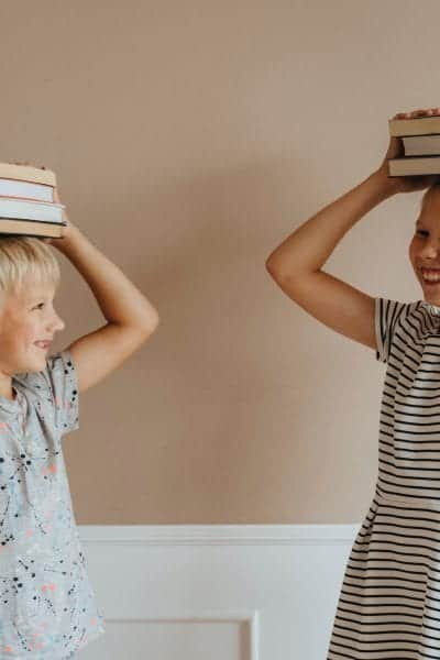 Pictured is a boy with short blonde hair holding four books on top of his head wearing a gray t-shirt with splattered, colorful dots on it. Next to him is a girl who is taller than the boy with her blond hair pulled into a bun holding three books on top of her head wearing a white and black striped dress. They are looking at each other and smiling.