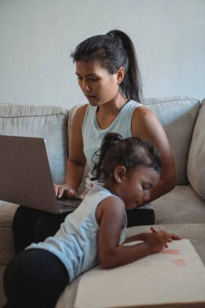 Time Management as a Busy Mom_Mom working at computer while daughter plays.jpg