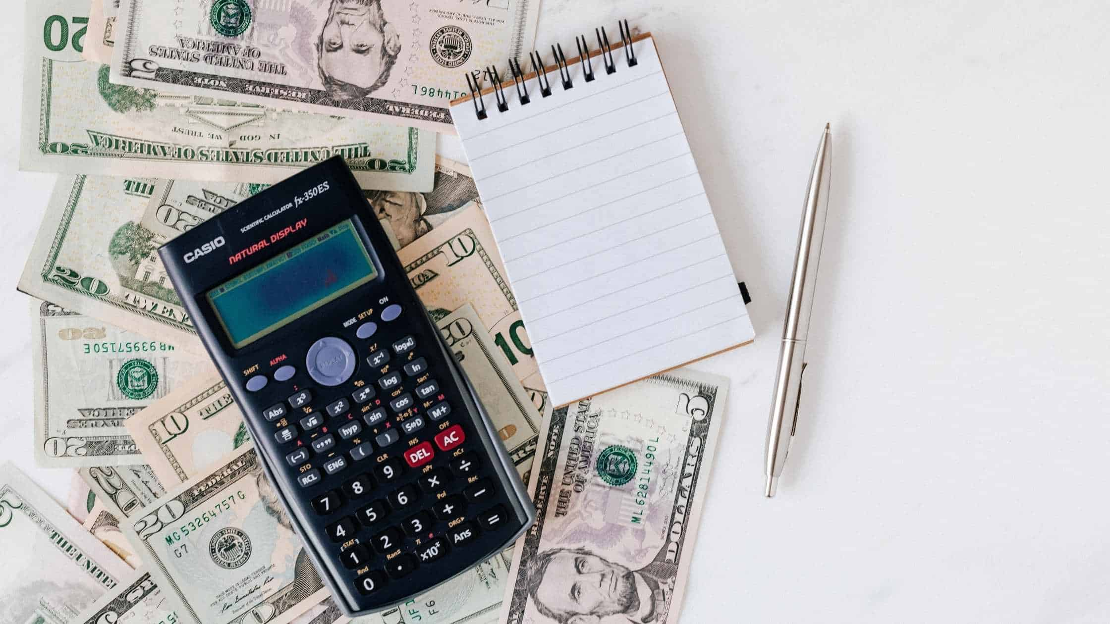 A black calculator, small notepad, and silver pen laid out on a table on top of a bunch of strewn money in the form of 5, 10, and 20 dollar bills