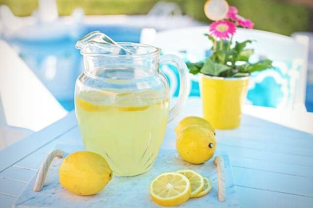 pitcher of lemonade on the table with three whole lemons and one sliced lemon and a pink flower in a yellow flower pot