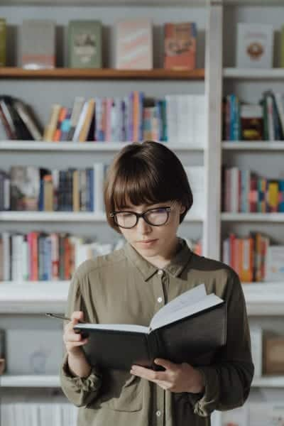 woman with short brown hair, bangs, and glasses reading a journal or book with a bookshelf full of books in the background