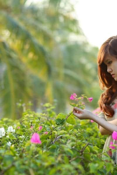 Picture of a woman with long brown hair pulled to the side wearing a gray dress with pink flowers on it standing outside in a patch greenery and pink flowers with a palm tree in the background.