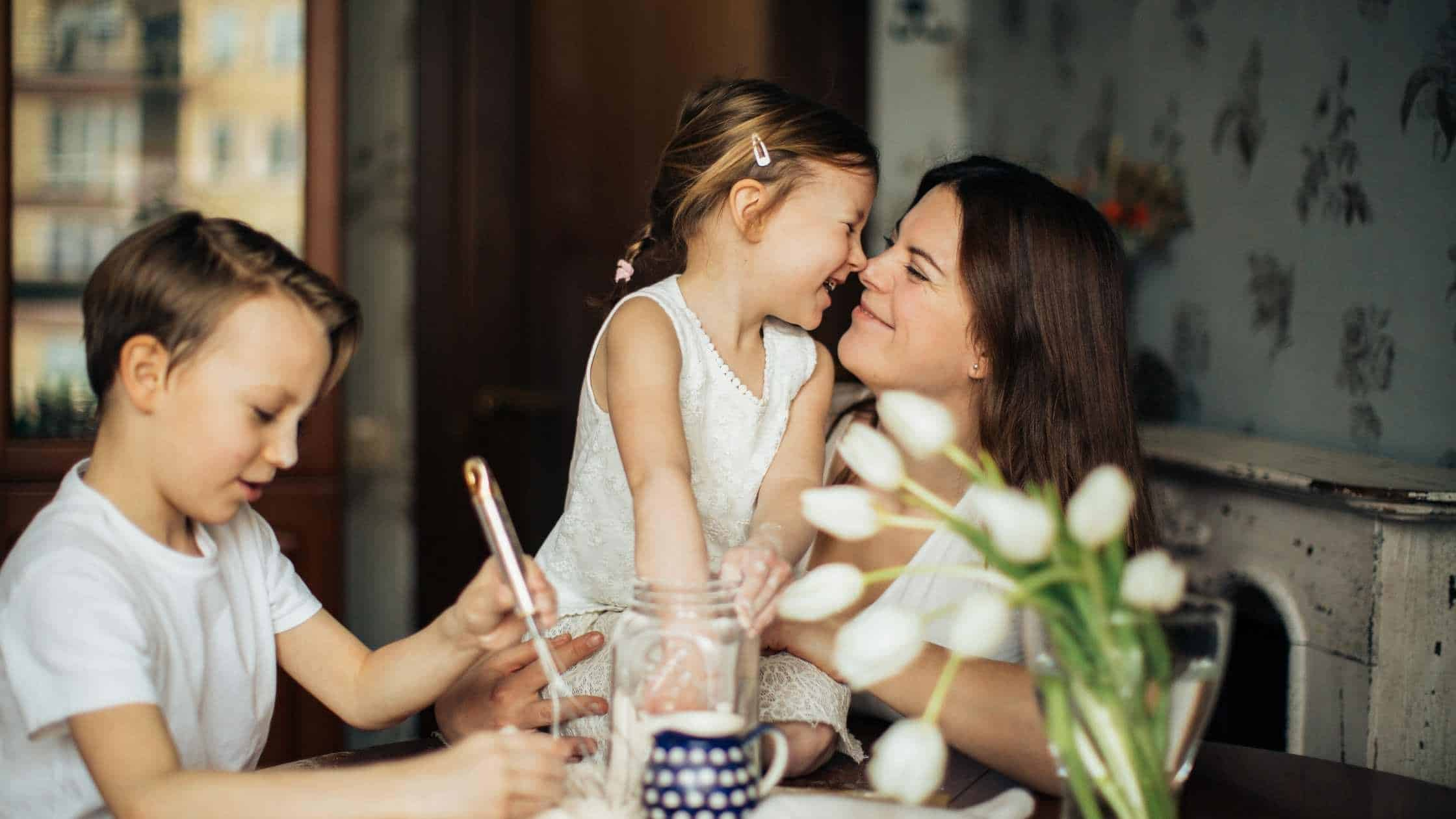 Mom sitting at table with her son and daughter while they work, daughter and mom give affection to each other