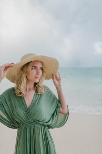 Tranquil woman in straw hat on sandy beach near sea