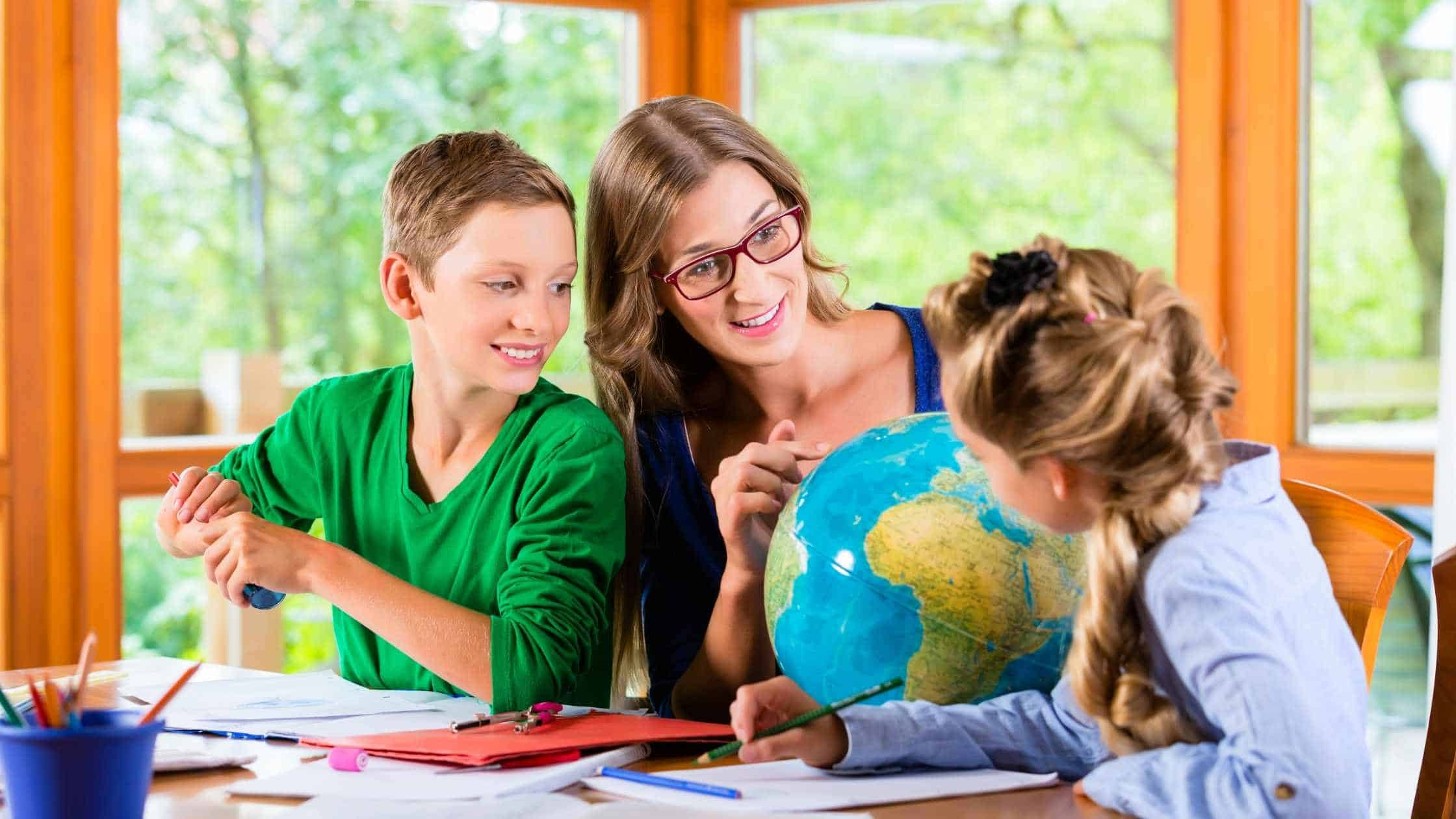 Mom sitting at table with son and daughter teaching them with a globe