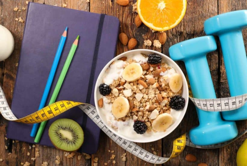 journal, measuring tape, oatmeal, and weights all strewn on a wooden table