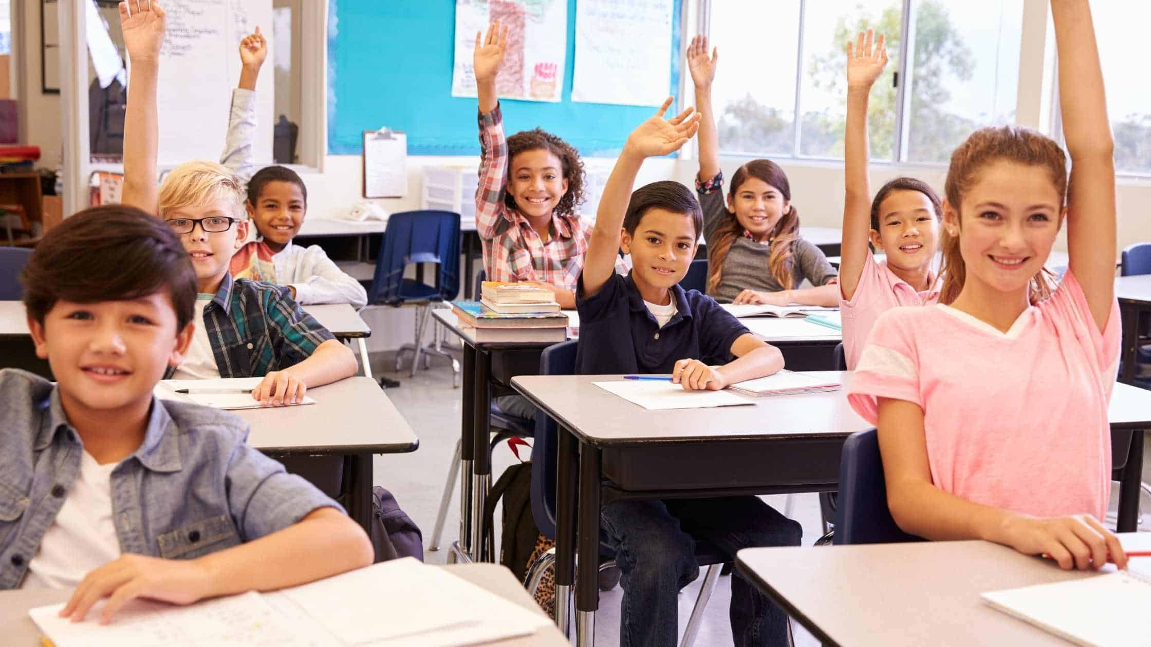 A classroom of kids sitting at their desks and raising their hands