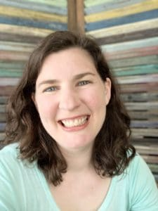 Woman with medium dark-brown hair wearing a sea-foam green shirt smiling. In the background is a colorful striped wall.