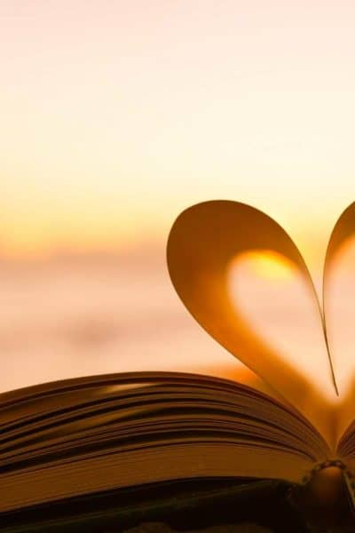 Sunset and ocean background with a book opens up and the pages shaping a heart