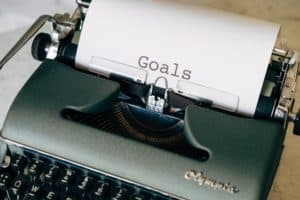 """gray typewriter with the words """"goal"""" on the paper in it"""
