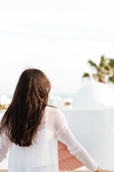Woman with long brown hair and a white long-sleeve blouse standing on a rooftop looking away into the distance