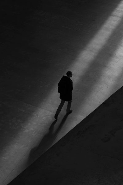 A picture in the dark with one light shining in to create shadows as a man walks in the distance